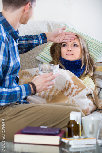 Fotografia  woman with cold lying on couch, boyfriend taking care