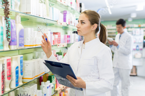 Poster Pharmacie Woman pharmacist looking medicine with notebook near shelves