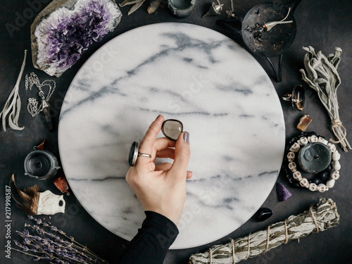Fotografie, Obraz  Witch's hand holding Smoky quartz above a marble white round tray