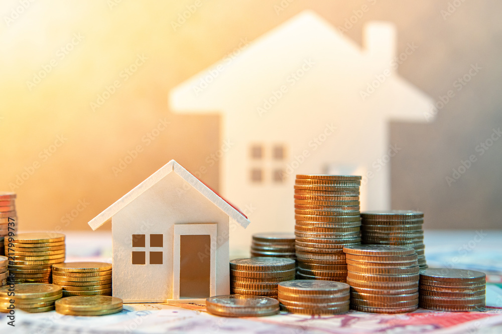Fototapeta Real estate or property investment. Home mortgage loan rate. Saving money for retirement concept. Coin stack on international banknotes with house model on table. Business growth background