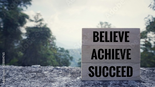 Poster de jardin Positive Typography Motivational and inspirational quote - 'BELIEVE, ACHIEVE, SUCCEED' written on wooden blocks. Blurred styled background.