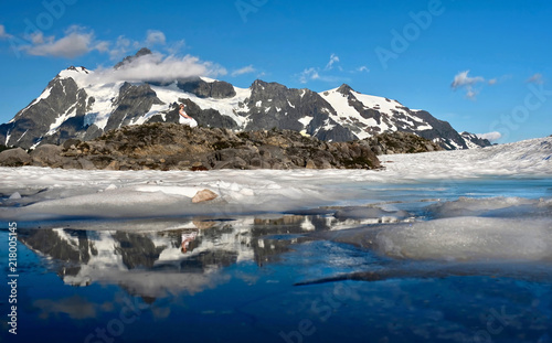 Printed kitchen splashbacks Glaciers Hiking in mountains in summer. Woman on rock by snow capped mountain reflecting in blue lake. Mount Shuksan on Artist Point. Mount Baker National Forest. Washington. United States of America.