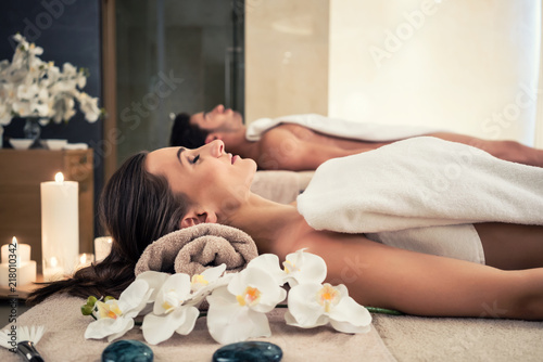 Fototapety, obrazy: Young man and woman lying down on massage beds at Asian luxury spa and wellness center