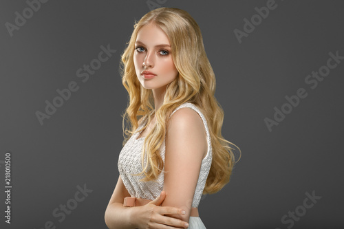 Vászonkép Beautiful woman with long blonde hair over gray background beauty female