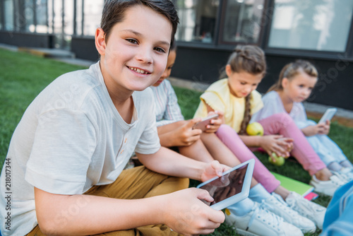 smiling schoolboy using tablet while sitting on grass with classmates Wallpaper Mural