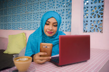 Young Beautiful And Happy Woman In Muslim Hijab Head Scarf Working With Laptop Computer And Mobile Phone Networking Running  Internet Business Online From Coffee Shop