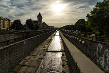 Regulierter Fluß, Bahnlinie Und Straße, Zum Horizont In Der Mitte Des Bildes Laufend, Darüber Die Untergehende Sonne
