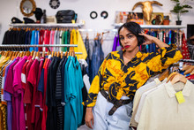 Stylish Woman Leaning On Rack In Shop