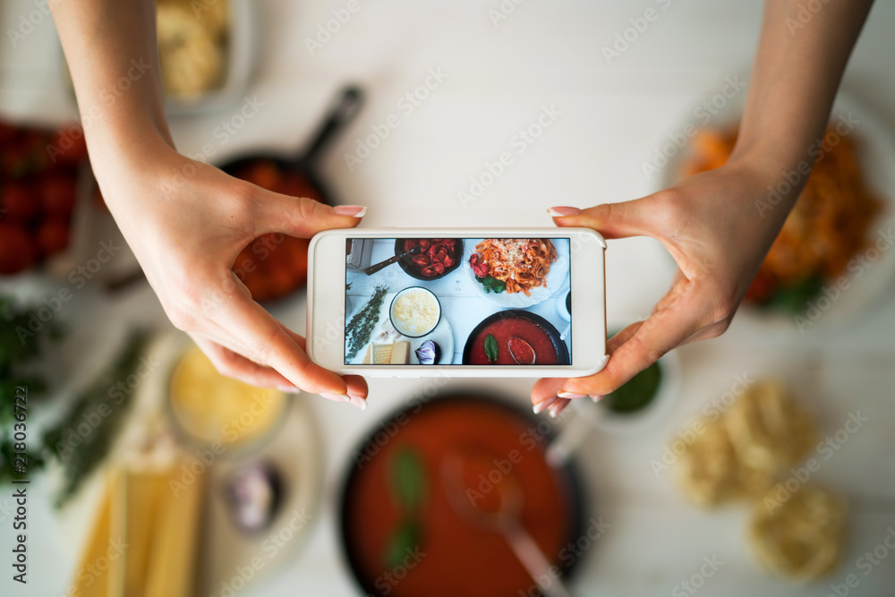 Fototapety, obrazy: Hands with the smart phone pictures of meal. Young woman, cooking blogger is cooking at the home kitchen in sunny day and is making photo at smartphone. Instagram food blogger workshop concept.