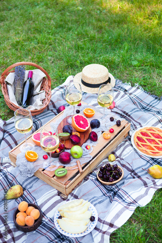 Foto op Aluminium Picknick Picnic background with white wine and summer fruits on green grass, top view