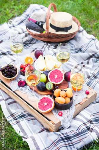 Aluminium Prints Picnic background with white wine and summer fruits on green grass, top view