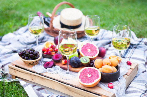 Garden Poster Picnic Picnic background with white wine and summer fruits on green grass, summertime party