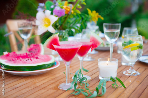 Family outdoor dinner in the garden in summer at sunset. Picnic food and drink concept