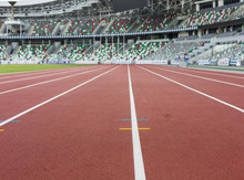 Red Sport Track For Running On Stadium With Tribune. Running Healthy Lifestyle Concept. Sports Background Abstract Texture