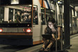 Portrait of young woman waiting at tram stop by night using tablet