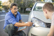 Learner driver with instructor checking headlight of a car