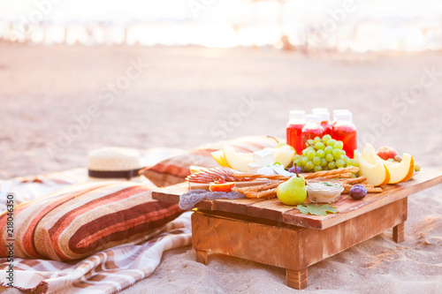 Picnic on the beach at sunset in the style of boho. Concept outdoors evening healthy dinnner with fruit and juice