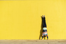 Acrobat Doing Handstand In Front Of A Yellow Wall