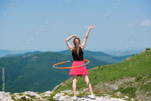 Photo  Young woman in pink skirts rotates hula hoop at the mountain top on beautiful nature background