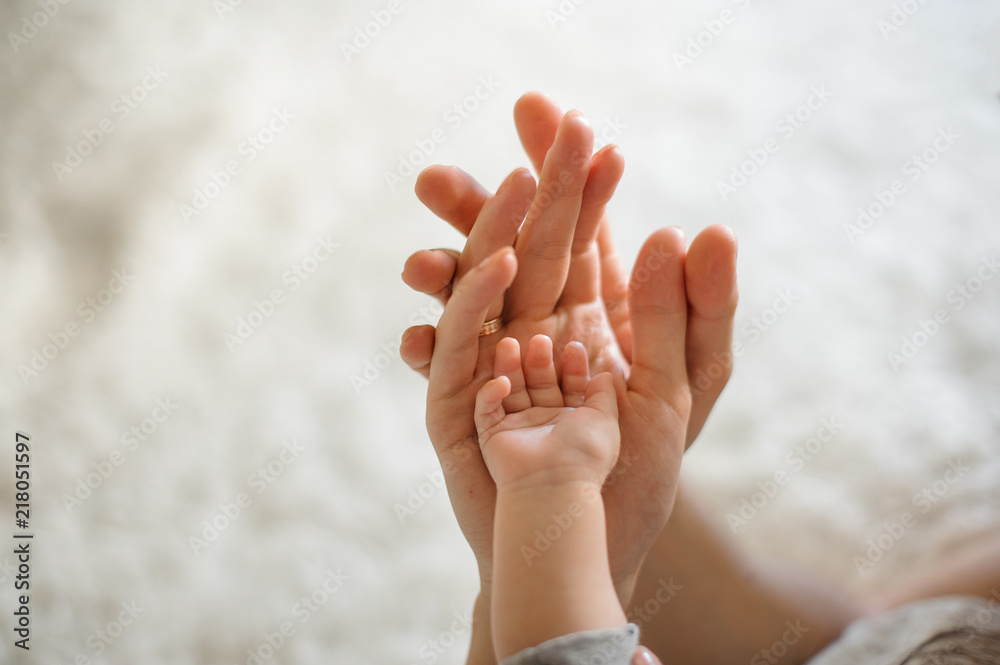 Fototapeta Close up of parents and baby join hands on the light background