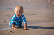 Little baby boy, playing on the ocean beach with toys