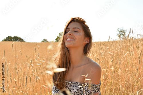 Fotografia, Obraz  joven y atractiva mujer sonriendo y mostrando felicidad en un campo de trigo al