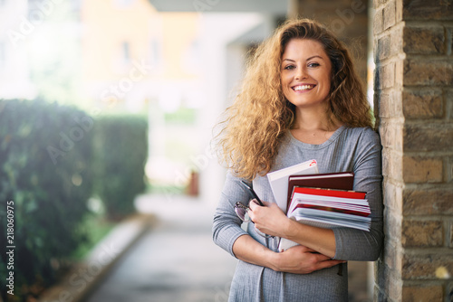Girl standing against the brick wall and holding book. Fototapete