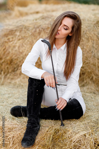 Fotografie, Obraz rider woman with whip is sitting on hay