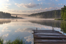 Sunrise Over The Foggy River With A Wooden Pier