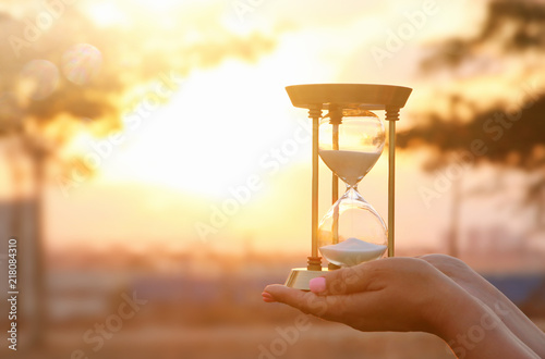 Young woman holding Hourglass during sunset. vintage style.
