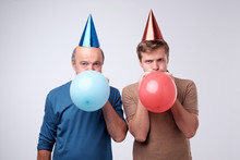 Mature And Young Men Blowing Up A Balloon For Birthday