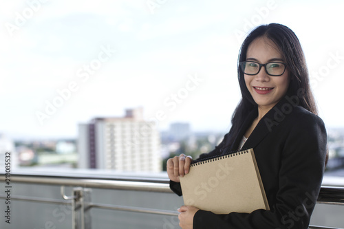 Photo  Young Asian business woman wear suit holding file document, standing at office
