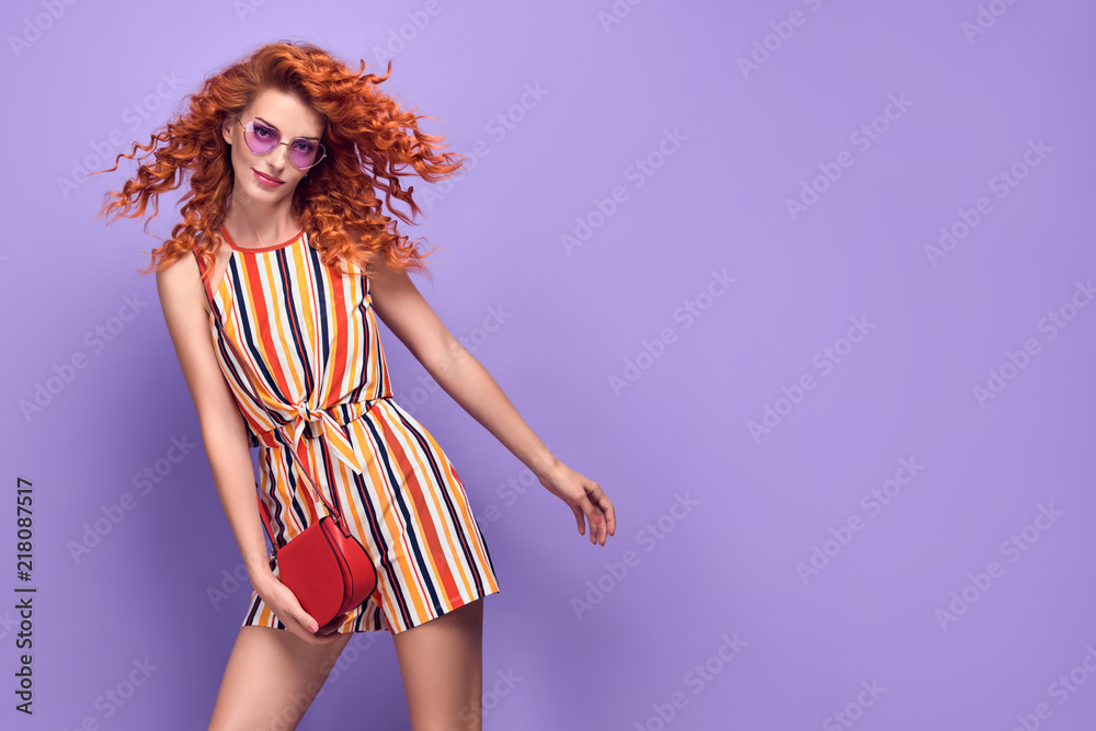 Fototapeta Young Pretty Redhead Girl Smiling in Studio on Purple. Beautiful woman in Stylish Summer Outfit, Trendy Curly Hairstyle, Fashion Sunglasses. Attractive Happy Model Having Fun