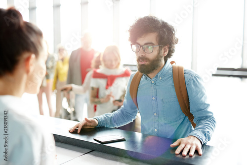 Fotografie, Obraz  Bearded adult man checking in and talking to staff at reception in airport