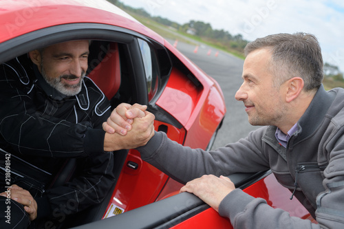 Fotografie, Obraz sportscar pilot shaking hands with his engineer on race track