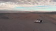 Aerial cinematic view of two people and car at road trip in sand desert Atacama Chile. People sitting and watching landscape at sunrise. Drone panning around car and people.