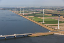 Aerial View Dutch Landscape With Bridge And Turbines Along The Coast