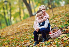 The Youngest Girl And Boy Go Through The Autumn Forest And Collect Mushrooms And Fruits.