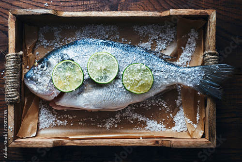 Fotografie, Obraz  Fresh raw sea fish dorado with salt and lime in wooden box top view