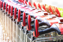 View Of Row Of Stacked Shopping Carts With Red Handles At Exit Of Supermarket At Day Mall On Parking Lot In Europe. Buy Food Supplies With Transport