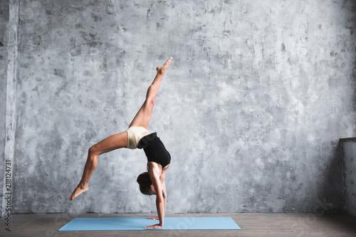 Dark-haired woman doing handstands Fototapet