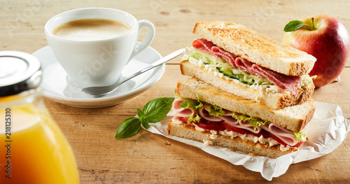 Fototapeta Cup of coffee and sandwich with ham on table obraz