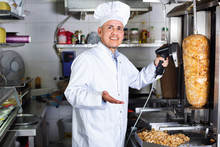 Cheerful Mature Man Cook Cutting Kebab Meat On Kitchen