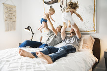 Family Of Four With Baby Having Fun On Bed