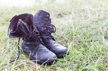 A Pair Of Old Worn Boots In The Grass