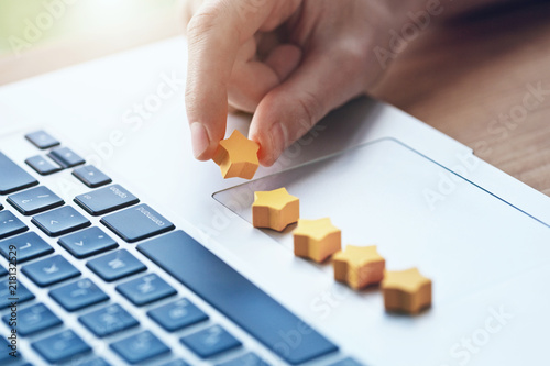 hand gives five stars rating as product feedback with laptop