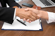 Woman shaking hands with real estate agent on meeting over table