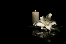 Beautiful Lily And Burning Candle On Dark Background With Space For Text. Funeral Flower