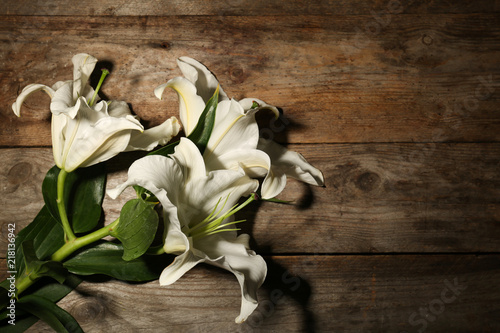 Fotomural  Beautiful lilies and space for text on wooden background