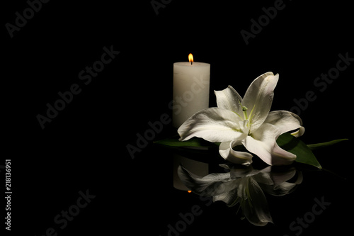 Canvas Print Beautiful lily and burning candle on dark background with space for text